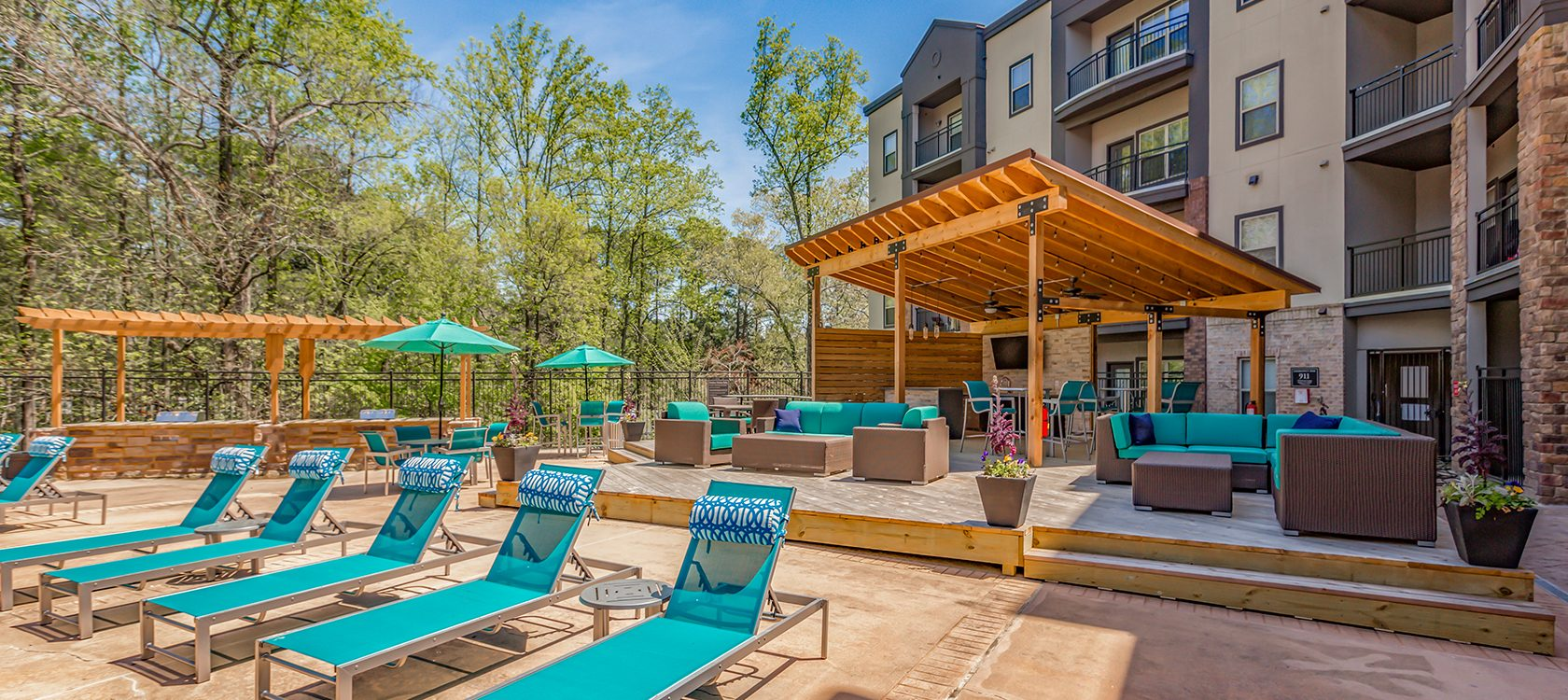 Bell Perimeter Center apartments pool area and outdoor kitchen shelf with umbrellas and lounge chairs